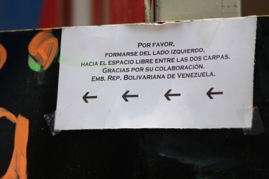Sign instructing people to line up to the left - by order of the Venezuelan Embassy. (Photo: Darren Popik)
